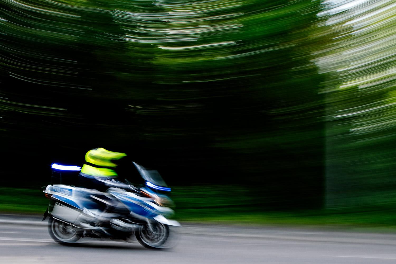 Beim VIVAWEST Marathon - Ein Polizist bolzt auf seinem Motorrad die gesperrte Straße hinunter. Er und seine Kollegen haben die Spitze der Läufer des VIVAWEST-Marathons gesichert.