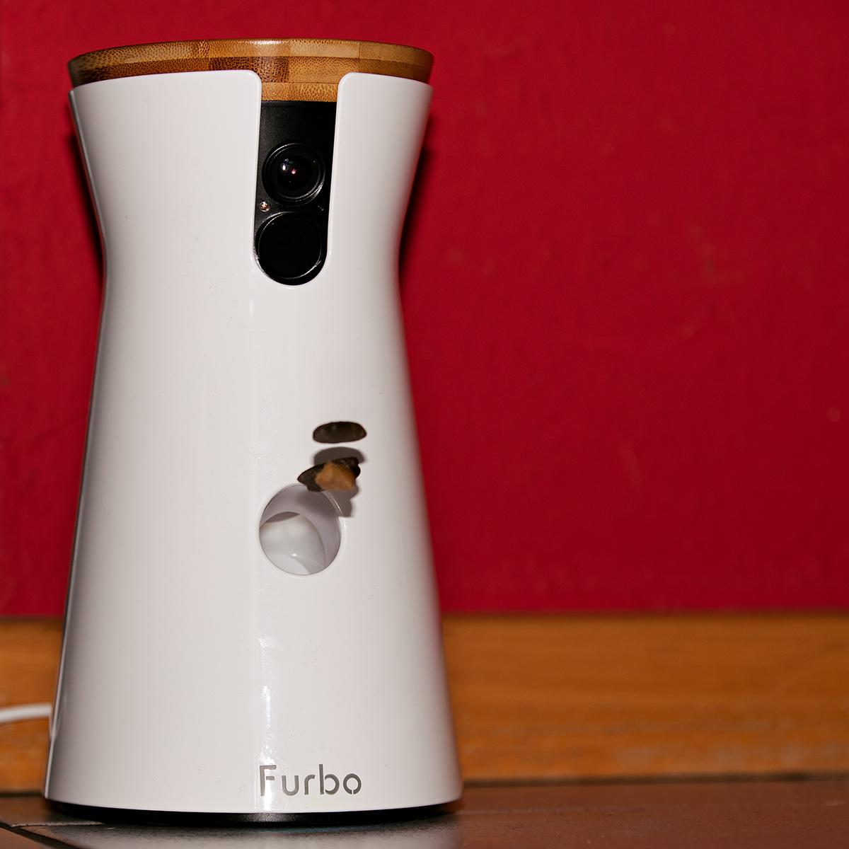 Furbo sieht aus wie eine Tulpenvase mit Deckel, kann aber einiges mehr. In einem 160 Grad Winkel überwacht Furbo den Raum. Über eine App könnt ihr ihre Aufnahmen sehen. Egal, wo ihre gerade seid. Hier wirft der kleine Schacht unten gerade ein paar Leckerchen aus.