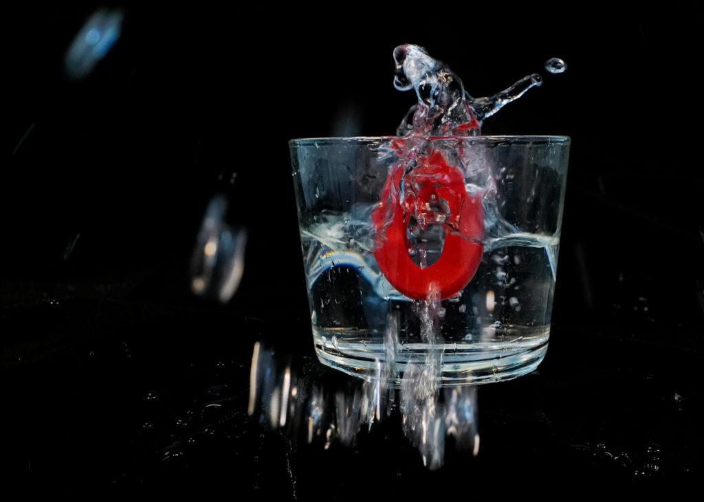 Ein Q fällt in ein Glas voller Wasser.