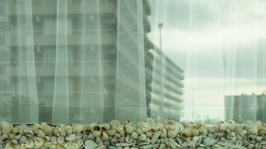 Das ist das Fenster eines Hauses, das im Schatten der Betonburgen steht.